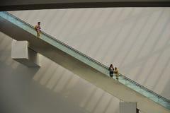 站立在商城的自动扶梯的人们 免版税库存照片