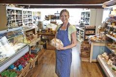 站立在商店的熟食所有者拿着面包 免版税库存照片