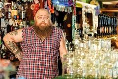 站立在啤酒吧的镇静有胡子的工作者 库存图片