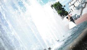 站立在喷泉的新娘夫妇 与拷贝空间的照片 免版税库存照片