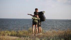 站立在困窘的年轻夫妇在享受海的看法小山 背包,远足者,旅客 后侧方视图 股票录像