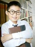 站立在图书馆走道的男小学生 图库摄影