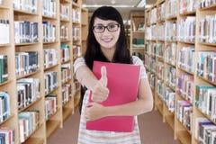 站立在图书馆里的美丽的学生 免版税库存图片