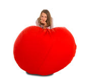 站立在圆形红色装豆子小布袋椅子附近的女孩 库存图片