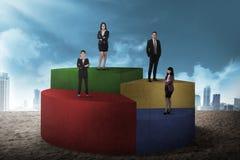 站立在圆形统计图表的企业队 图库摄影