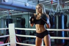 站立在圆环的年轻俏丽的拳击手妇女 免版税库存照片