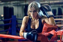 站立在圆环的年轻俏丽的拳击手妇女 库存照片