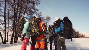 站立在圈子的一个小组登山人和与他的手谈论,打手势,他的在地图的路线 在背景中 股票录像