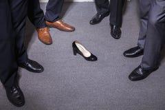站立在圈子的商人在仅妇女的高跟鞋、脚和腿附近 免版税库存图片