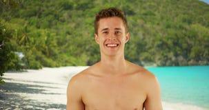 站立在圣约翰海岛海滩的年轻白种人男性特写镜头画象  库存图片