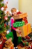 站立在圣诞树和举行箱子附近的女孩有礼物的 库存照片
