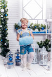 站立在圣诞树和Christm旁边的微笑的小女孩 库存照片