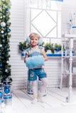 站立在圣诞树和Christm旁边的微笑的小女孩 图库摄影