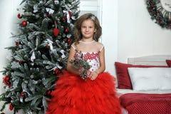 站立在圣诞树附近的红色和白色礼服的公主 免版税图库摄影