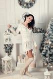 站立在圣诞节的愉快的年轻深色的妇女近的杉树 免版税库存照片