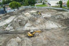 站立在地面的黄色挖掘机在一个新的大厦的建筑时在城市区域 在a的鸟瞰图 库存图片