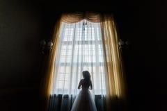 站立在城堡窗口附近的后面观点的新娘 库存照片