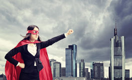 站立在城市前面的女性超级英雄 库存图片