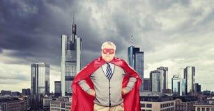 站立在城市前面的骄傲的成熟超级英雄 免版税库存照片