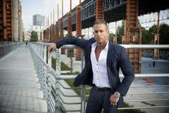站立在城市环境里的英俊的肌肉白肤金发的人 免版税库存图片