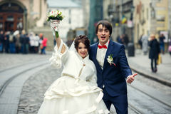 站立在城市的电车方式之间的滑稽的新婚佳偶微笑 免版税库存图片