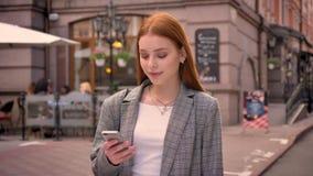 站立在城市街道上和键入在电话的年轻俏丽的姜妇女,微笑,修造有咖啡馆背景 股票视频