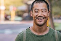 站立在城市街道和微笑上的英俊的亚裔人 免版税库存照片