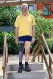 站立在培训班楼梯的资深腿被截肢者实践的 免版税库存图片
