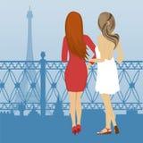 站立在堤防和神色的两名妇女背面图在艾菲尔铁塔在巴黎 免版税库存图片