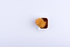 站立在塑料conta的红色垂度调味汁的唯一鸡块 免版税库存照片