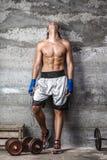 站立在墙壁上的肌肉拳击手人 免版税库存图片