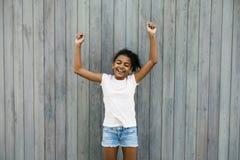 站立在墙壁的愉快的女孩 库存照片