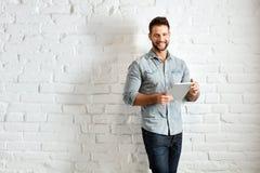 站立在墙壁的年轻人使用片剂 免版税库存图片