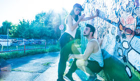 站立在墙壁的年轻夫妇在一个城市环境里 图库摄影
