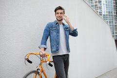 站立在墙壁背景的一件蓝色牛仔布夹克的人 在橙色自行车附近的年轻人 有袋子的微笑的学生 免版税库存图片
