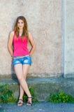 站立在夏日拷贝空间的混凝土墙的美丽的十几岁的女孩 库存照片