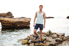 站立在多岩石的海滩的年轻英俊的人运动员 免版税库存照片