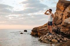 站立在多岩石的海滩的年轻英俊的人运动员 库存照片