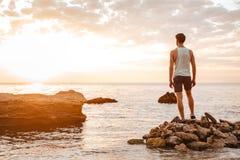站立在多岩石的海滩的年轻英俊的人运动员 免版税图库摄影