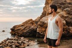 站立在多岩石的海滩的年轻运动员在海旁边 免版税库存图片