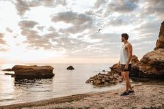 站立在多岩石的海滩的年轻运动员在海旁边 库存照片