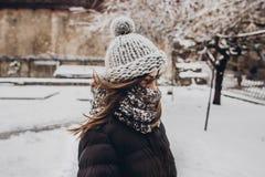 站立在多雪的城市stre的被编织的帽子的时髦的行家妇女 免版税库存照片