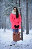 站立在多雪的fo的一件桃红色夹克和一条白色围巾的一个女孩 免版税图库摄影