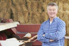 站立在大包和老农场设备前面的农夫 免版税库存照片