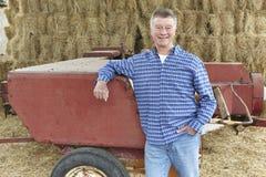 站立在大包和老农场设备前面的农夫 库存照片