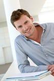 站立在大厅里的微笑的英俊的人 库存照片