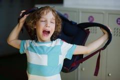 站立在大厅里的疲乏的矮小的学生在衣物柜附近和佩带背包 免版税库存照片
