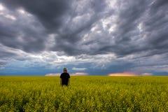 站立在大开农田的孤立人在风暴期间 免版税库存照片
