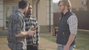 站立在大房子饮用的啤酒前面的白种人和非裔美国人的人画象  一个人完成了他的 股票录像