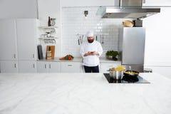 站立在大现代厨房的老练的男性厨师厨师,当使用巧妙的电话时 免版税库存照片